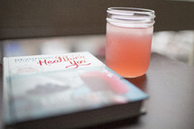 An iced beverage next to a book about health.
