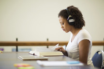 a woman reading a book and listening to headphones
