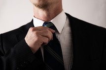 a man straightening his tie