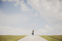 Girl walking down a dirt road carrying luggage