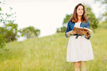 woman standing in a field reading a Bible