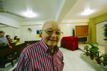 An elderly man greeting people in church