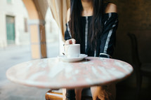 woman sitting at a table alone with a coffee mug