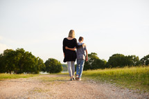 a mother walking with her son down a dirt road