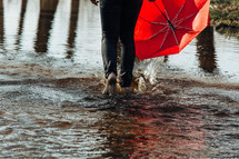woman walking through a puddle carrying an umbrella