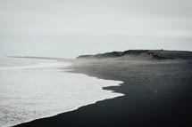 tide washing onto a black sand beach