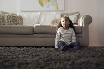 a girl child sitting on a rug in a living room