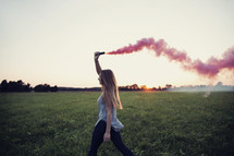 young woman walking holding a smoke flare