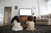 kids watching television in a living room.