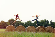 man and woman running on hay bales