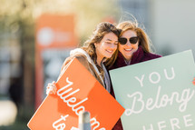 women holding signs - welcome, you belong here