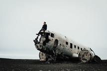 a man sitting on a wreckage of an airplane crash site