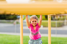 Elementary girl on the monkey bars, smile, joy, back to school, happy, playground