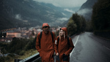 a man and woman in rain gear walking down a mountain road