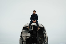a man sitting on wreckage of an airplane crash site