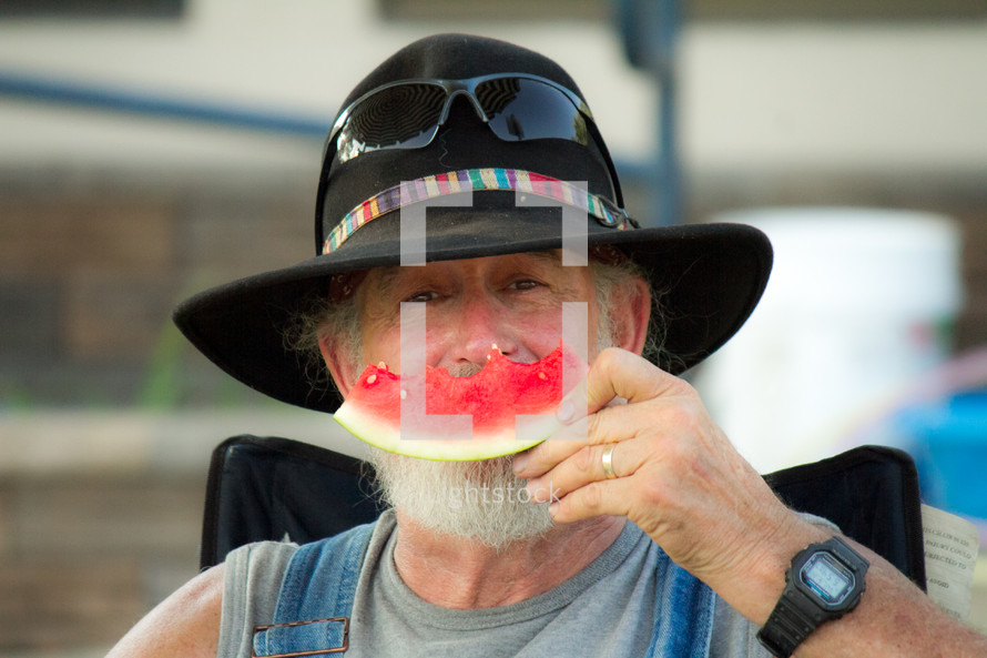 man in a hat eating watermelon