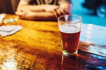 Glass of beer on a bar.