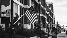 row of American flags on flag poles on lamp posts along a sidewalk