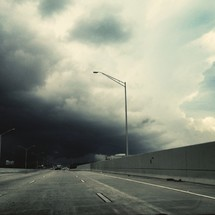street light over a highway under a stormy sky