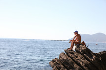 A fisherman sitting on a rock fishing