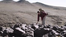 a man hiking up a desert mountain