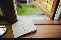 Open bible on window sill