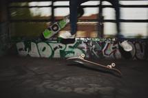 Feet and skateboard midair in grafitti garage.