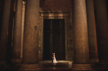 bride and groom between columns in the lobby of an elegant building