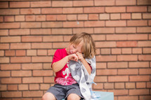 a nervous child with his security blanket crying sitting on a school locker