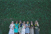 women holding sunflowers in front of an ivy wall