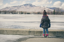 a child staring at a frozen lake