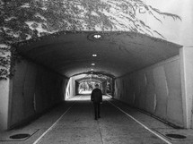 man walking through a tunnel