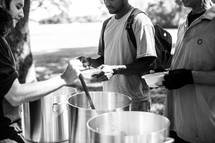 serving soup at a soup kitchen outdoors