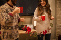 a couple holding mugs of hot cocoa and a Christmas sign