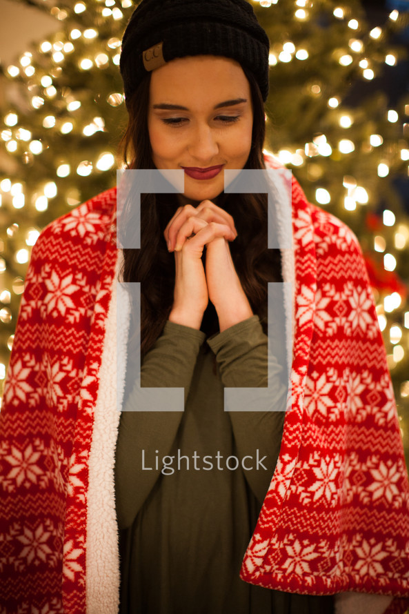 a woman standing in front of a Christmas tree with praying hands