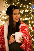 a woman with a mug of hot cocoa standing in front of a Christmas tree