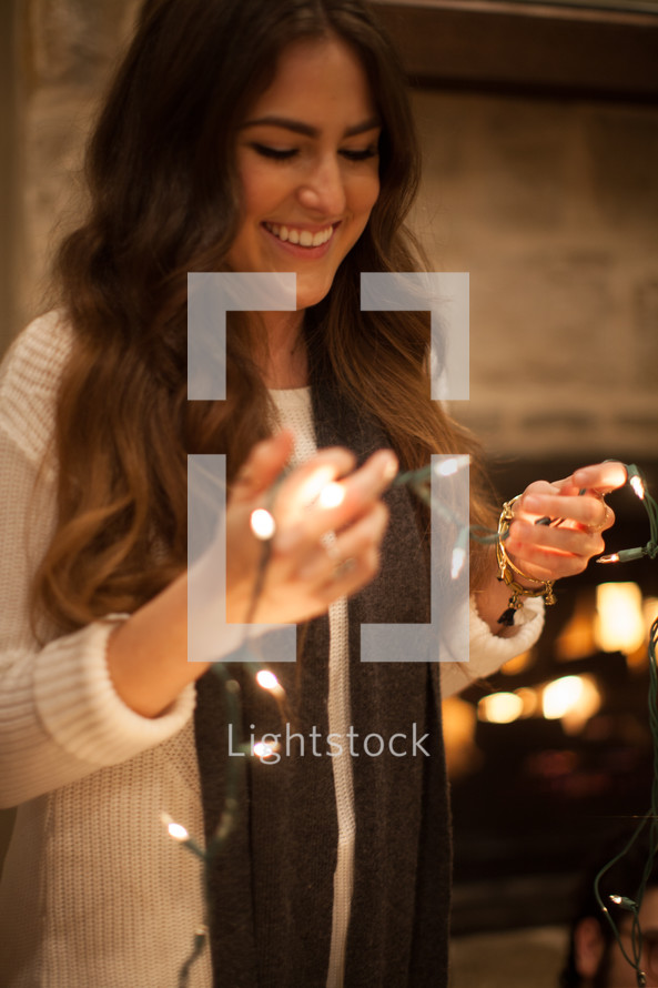 a woman hanging Christmas lights
