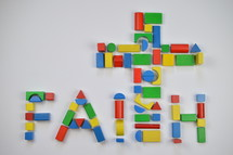word faith cross of colorful toy wooden blocks