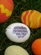 eggshell in the gras with a piece of the bible inside saying: HE HAS RISEN! between colored eggs,