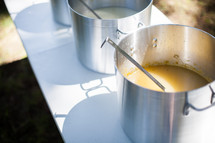 stock pots of soup on tables at a soup kitchen
