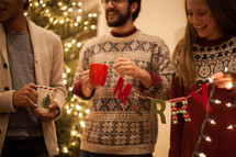 people drinking hot cocoa and talking at a Christmas party