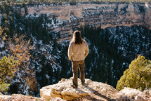 a man standing at the edge of a cliff looking down