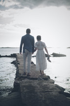 a couple walking on a jetty
