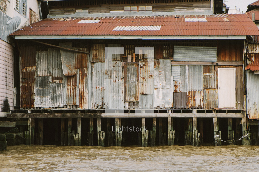 Tin walls of a shed on stilts above a river in Thailand.