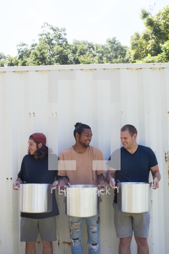 men holding stock pots at a soup kitchen