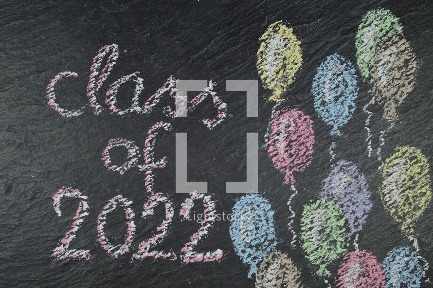 chalk on slate with balloons and the words: class of 2022