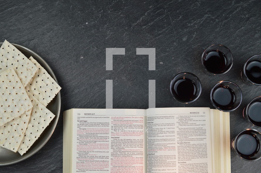 open Bible, unleavened bread, and communion wine cups