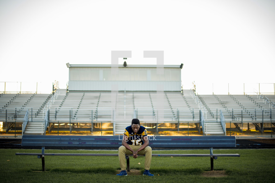 young man in his football jersey praying