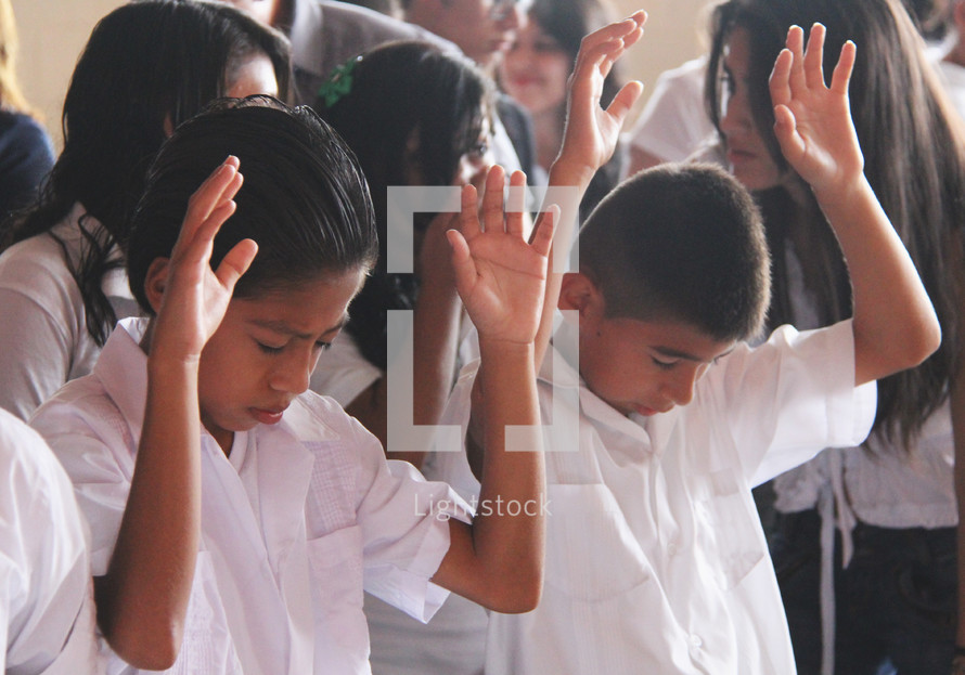 latino children with hands raised praising God