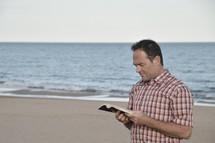 a man reading a Bible on a beach